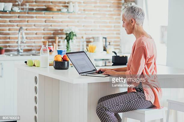 Older Caucasian woman using laptop in kitchen