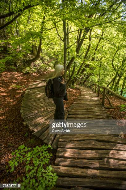 Older Caucasian woman walking on wooden pathway in forest