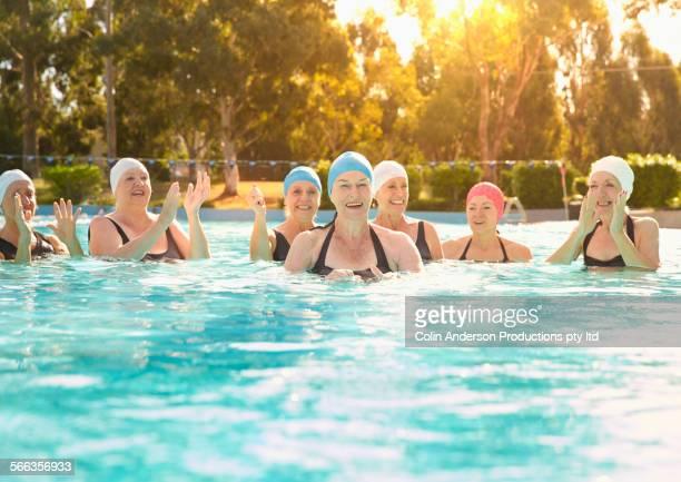Older Caucasian women cheering in swimming pool