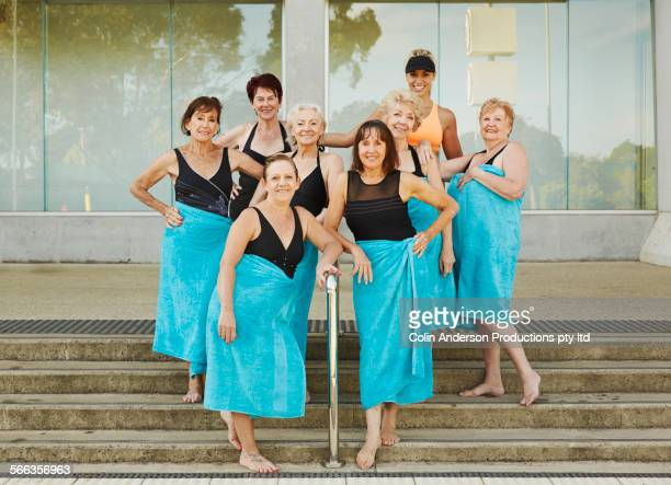 Older Caucasian women in towels smiling at pool