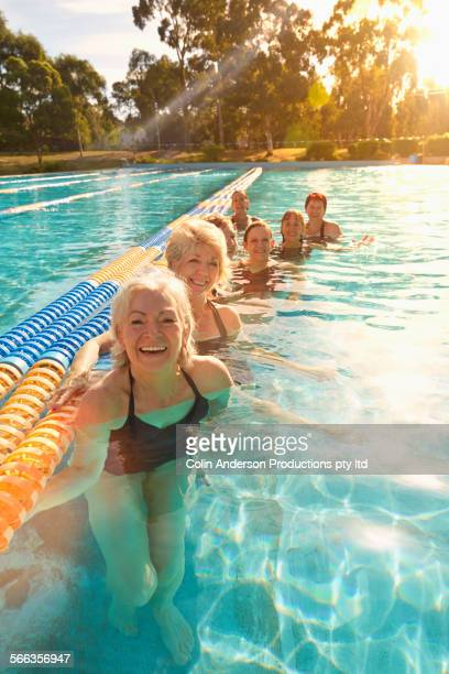 Older Caucasian women smiling in pool