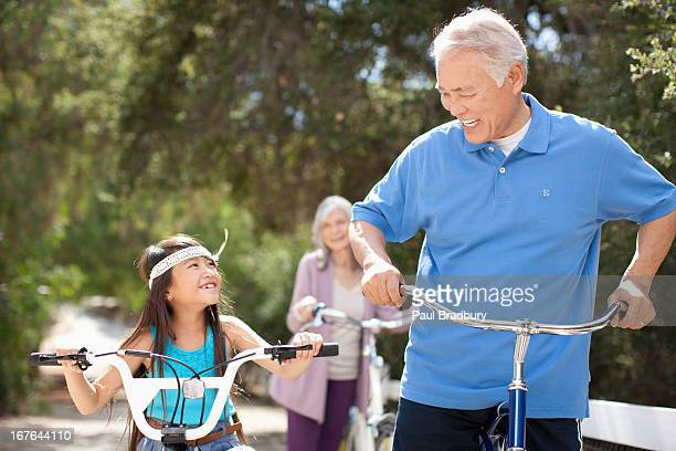 Older couple and granddaughter riding bicycles outdoors