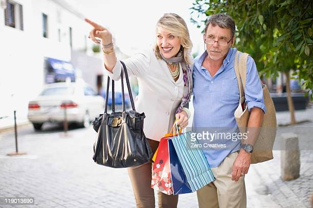 couple de retraités transportant des sacs de shopping