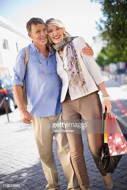 Vecchia coppia che trasportano borse per gli acquisti