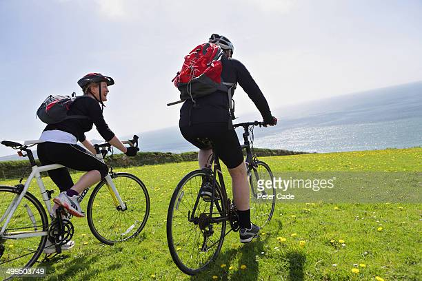 Older couple cycling in field with sea view