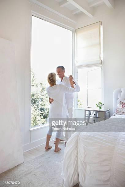 Older couple dancing in bedroom