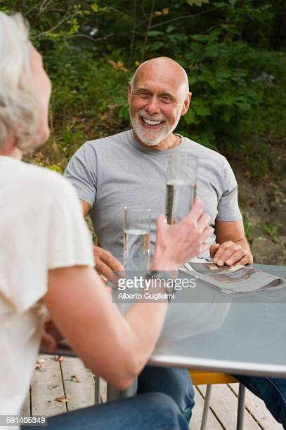 Older couple drinking water at table outdoors