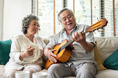 Happy Retirement Older Couple enjoying with singing and guitar together. Having fun.