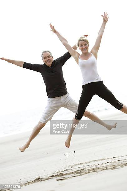 Older couple exercising on beach, star jumps