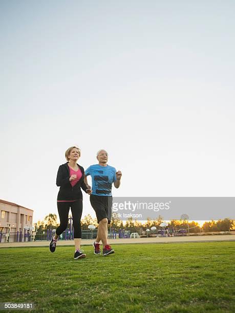 Older couple jogging together in urban park