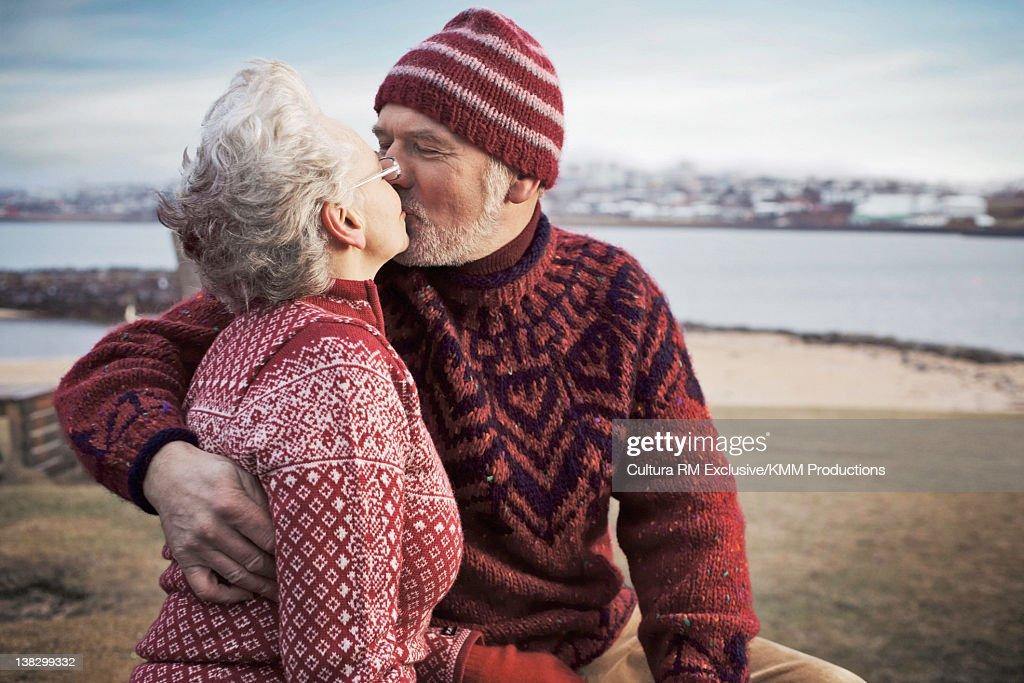 Older couple kissing on beach