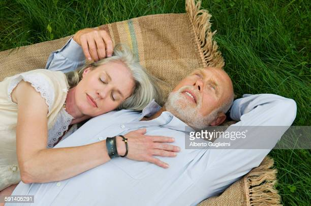 Older couple napping on picnic blanket