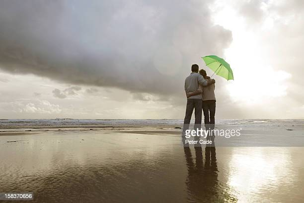 Older couple on beach with umbrella looking at sea