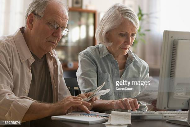 Older couple paying bills on computer