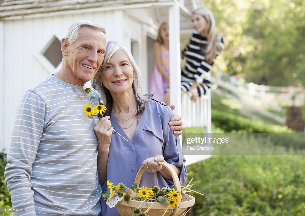 Older couple picking flowers outdoors : Stock Photo