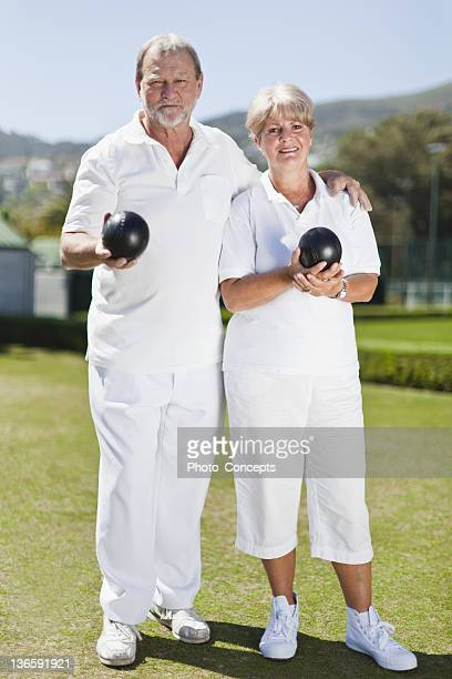 Older couple playing lawn bowling