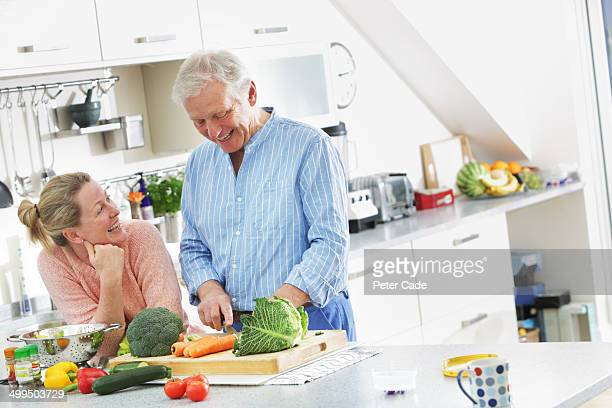 Older couple preparing food in kitchen
