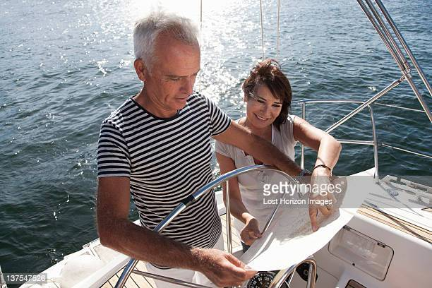 Older couple reading map on sailboat