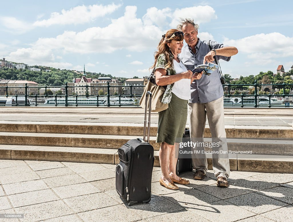 Older couple reading travel guide : Stock Photo