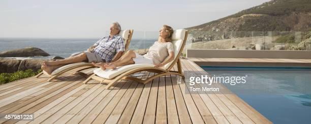 Älteres Paar Entspannung in Liegestühlen am pool