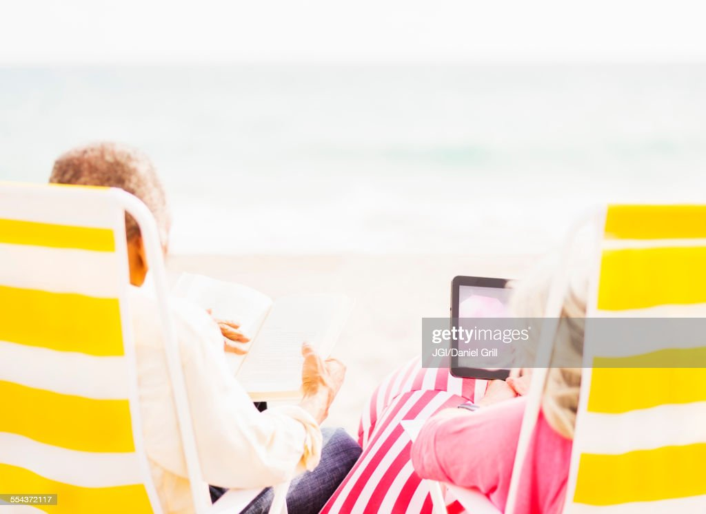 Older couple relaxing in lawn chairs on beach