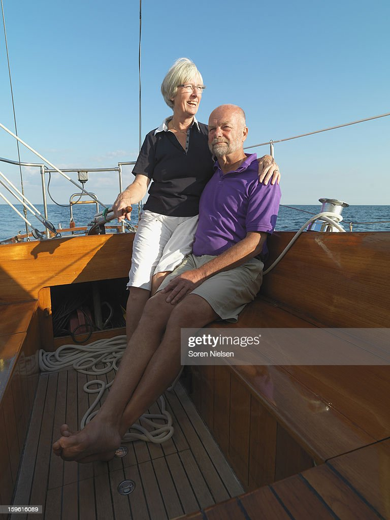 Older couple relaxing on sailboat : Stock Photo