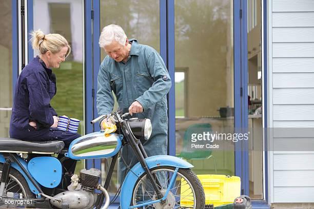 Older couple repairing old motor bike