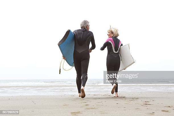 Older couple running into sea wih bodyboards
