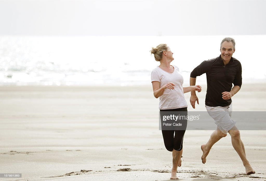 Older couple running on beach, happy, playing : Stock Photo