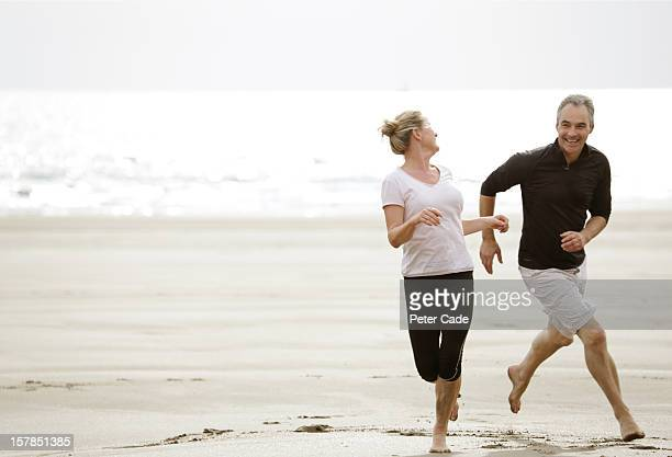 Older couple running on beach, happy, playing