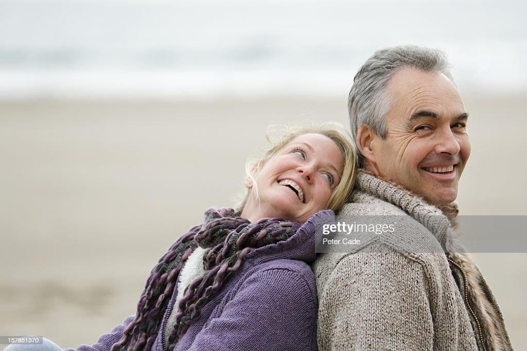 Older couple sat back to back on beach smiling