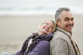 Older couple sat back to back on beach smiling