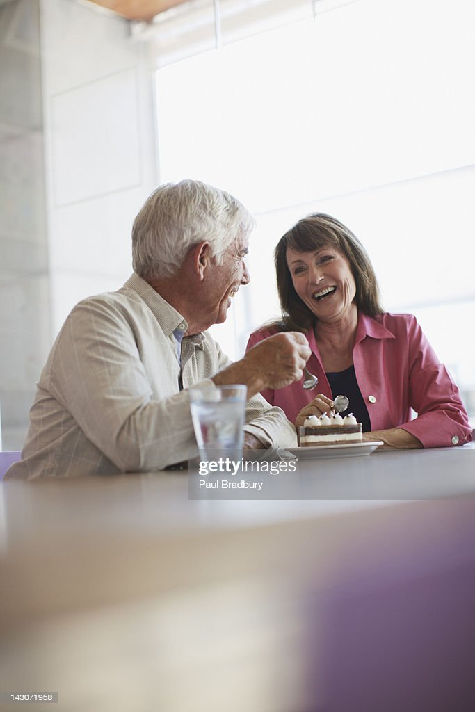 Older couple sharing dessert in cafe : Stock Photo