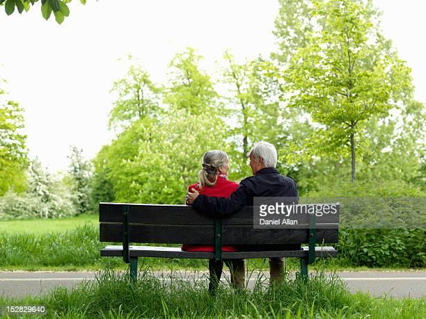 Older couple sitting on park bench