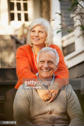 Older couple sitting on steps outdoors : Stock Photo