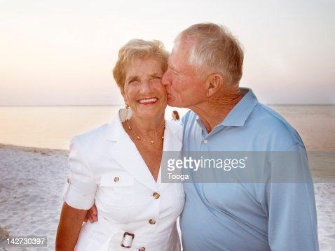 Older couple standing on beach : Stock Photo