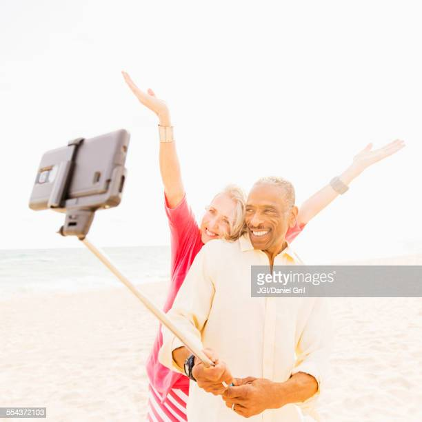 Older couple taking cell phone photograph on beach