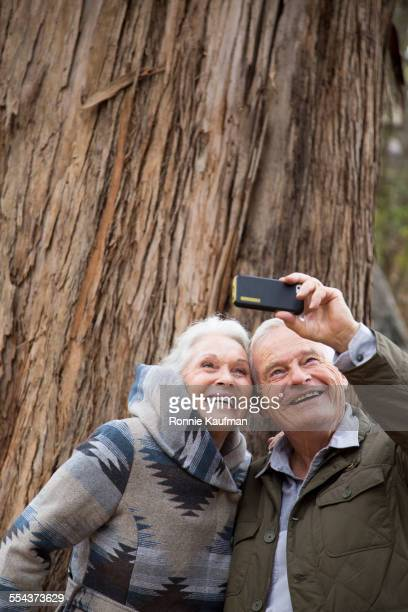 Older couple taking photographs together in park