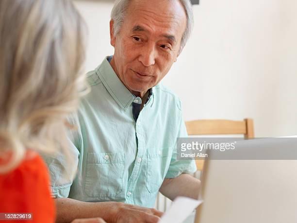 Older couple talking in kitchen