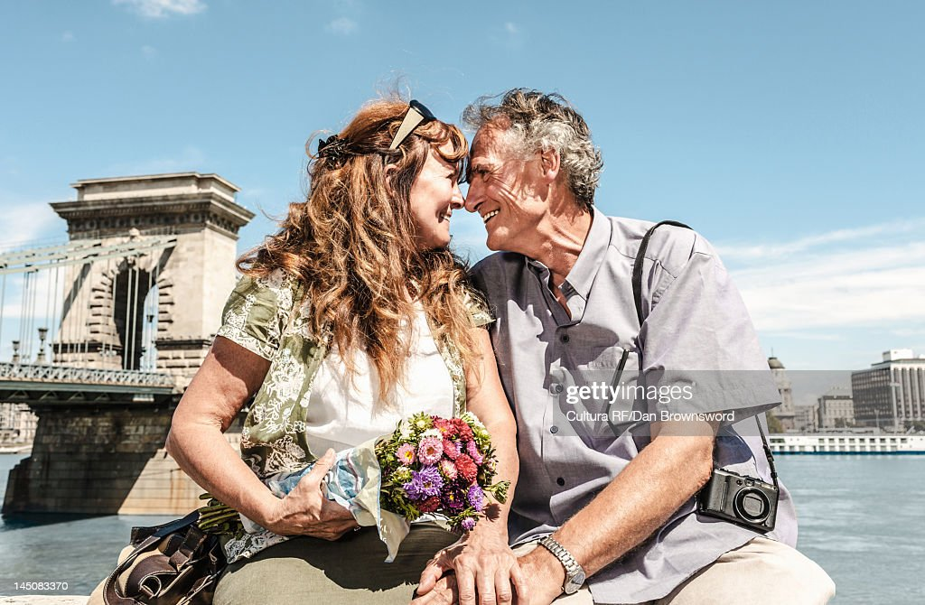 Older couple touching noses on bridge : Stock Photo
