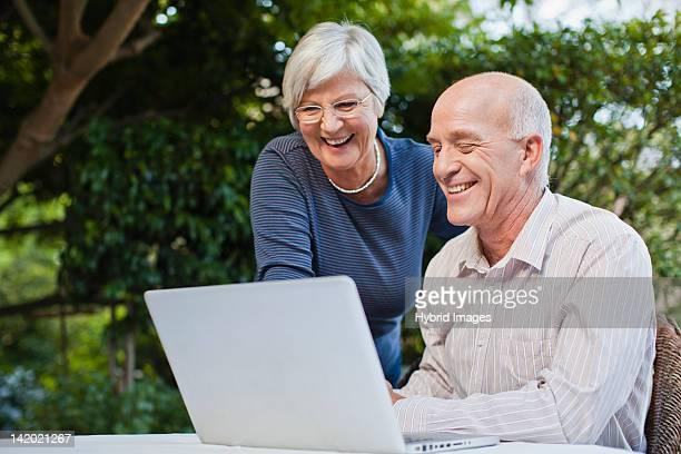 Older couple using laptop outdoors