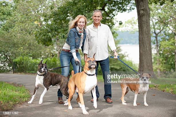 Older couple walking dogs in park