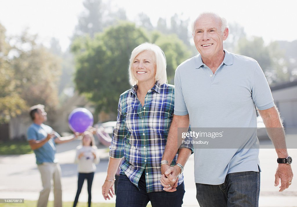 Older couple walking together outdoors : Stock Photo