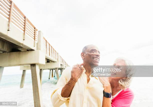 Older couple walking under boardwalk on beach