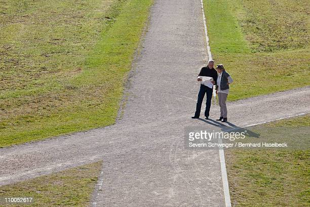 Older couple with map at a crossroads