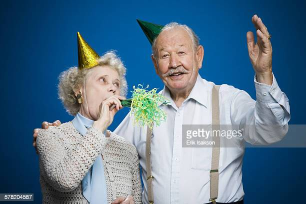 Older couple with noisemakers and party hats