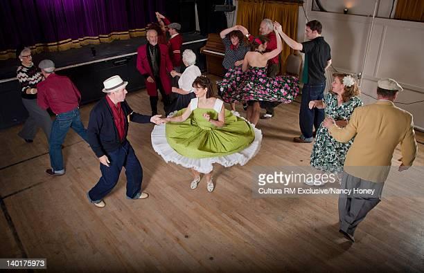 Older couples dancing in auditorium