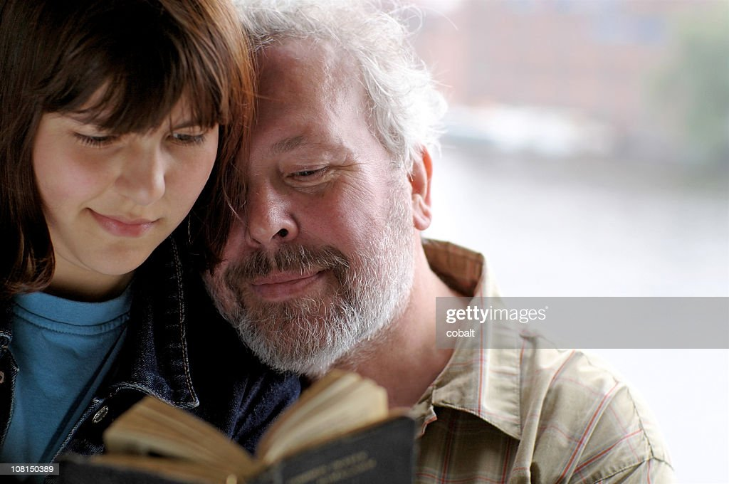 Older Father and Daughter Reading from Vintage Book Together : Stock Photo