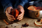 Older female hands holding a glass mug with hot mulled wine next to the steaming cooking pot,  Christmas ingredients, orange slices, cinnamon sticks, star anise and cloves, a warming home scene on a r