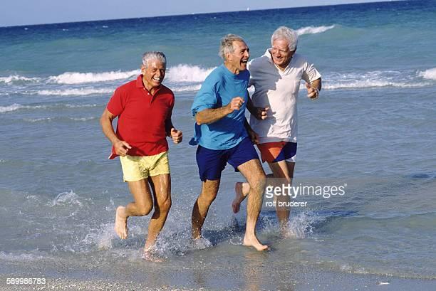Older guys running on the beach
